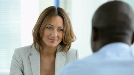 praca : African-American man seen from his back taking part in a job interview or a business meeting talking to a smiling lady