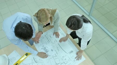 discussão : Overview of a business team working on a blueprint of a high-end device