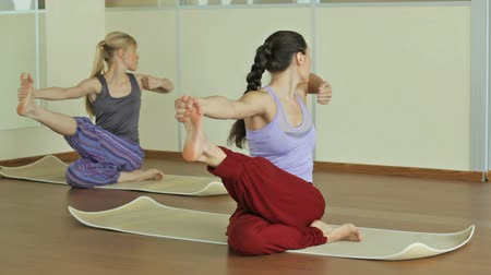 kadınlık : Two beautiful women practicing yoga indoors