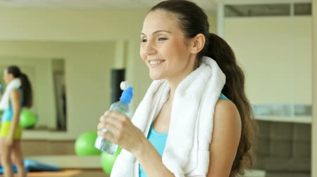 suor : Young brunette smiling at camera and drinking water after intense workout Vídeos