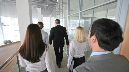 career success : Rearview of five business people in motion, the leader looking at his watch