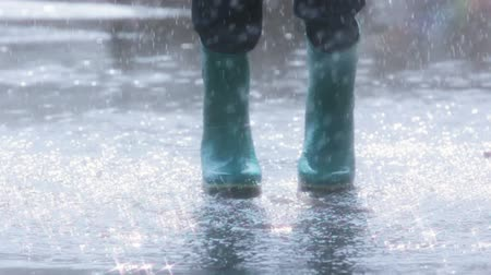 stříkající : Slow motion of a child in rubber boots jumping in the middle of the puddle