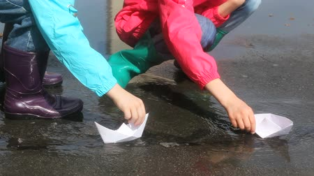 przedszkole : Children playing with paper boats after the rain