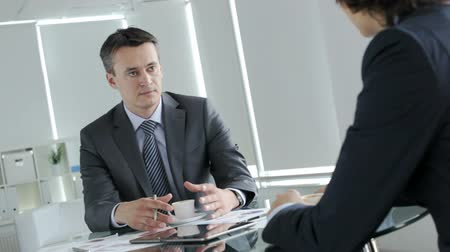 confiança : Handsome businessman telling his colleague about contemporary business issues