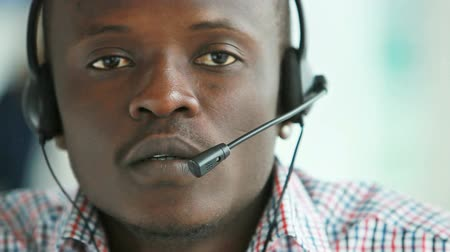 temsilci : Close-up of African-American guy wearing headphones with mic working for support service Stok Video