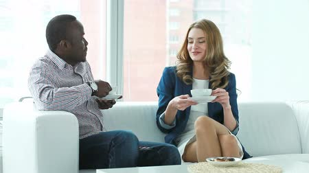 dialog : Guy and girl sitting on the sofa, chatting and having tea Wideo