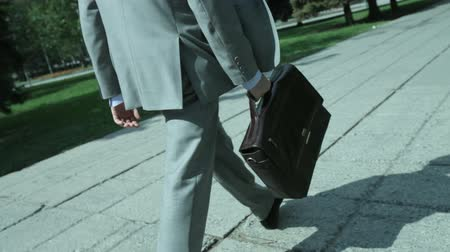 идущий : Busy businessman walking along the street carrying a briefcase