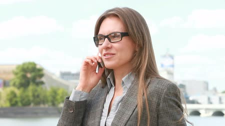 caucasiano : Beautiful businesswoman talking on the phone outside in urban environment