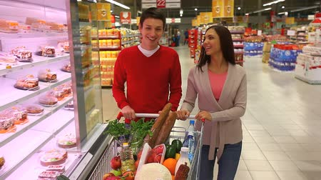 grocery : Young people doing shopping together in a modern big supermarket