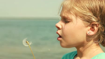 üfleme : Girl blowing a dandelion off making a wish