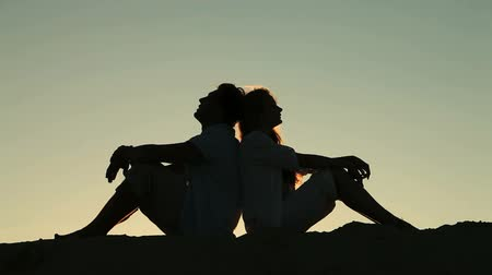 comfortable : Silhouettes of lovers sitting back to back against clear evening sky, concepts of love and trust