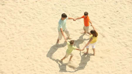 birlik : Excited family dancing together in a ring on the beach Stok Video