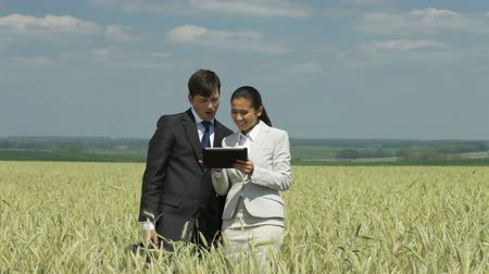 társult : Business team standing in the wheat field and using a digital tablet to find the best solution