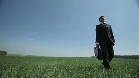 biznesmeni : Peaceful businessman walking towards the camera in rural surroundings Wideo