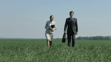 collaborator : Positive business woman and her colleague strolling in the grass field Stock Footage