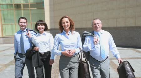 négy ember : Business group of four walking towards the camera, female leader being in the front