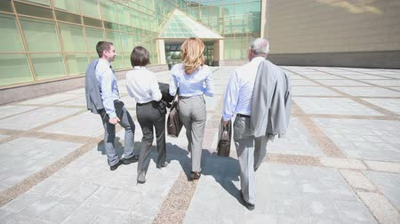 четыре человека : Confident business team walking steadfastly outside in urban surroundings