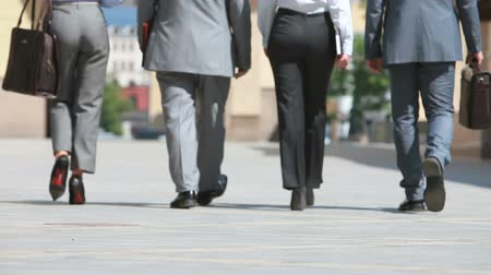 unrecognizable people : Confident business people viewed from the back walking in step
