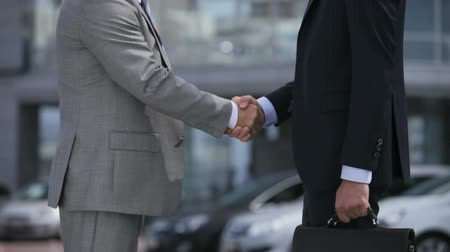 homem de negócios : Business people shaking hands and moving towards the office building