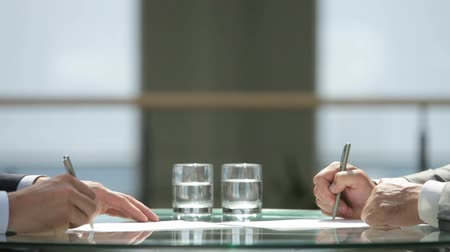 collaboration : Business people signing the contracts together concluding the deal by a firm handshake Stock Footage