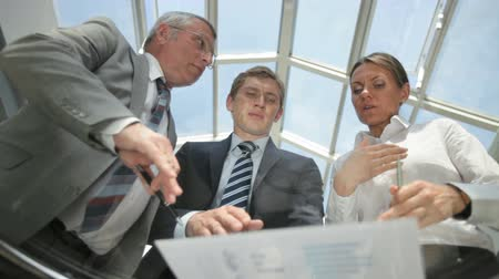 dialog : Serious business people viewed from below discussing financial data