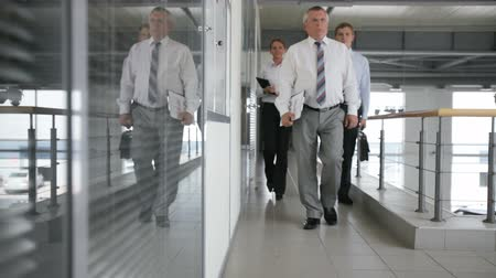 компания : Confident team of three walking along the corridor of the office building