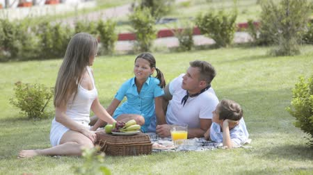 пикник : Parents having a picnic together with their kids