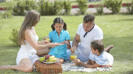 пикник : Cheerful family sitting on the grass having a snack