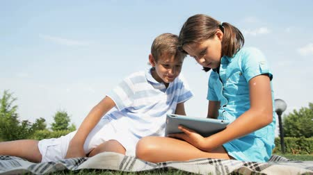 outside : Cute girl explaining to his brother how to use a tablet pc