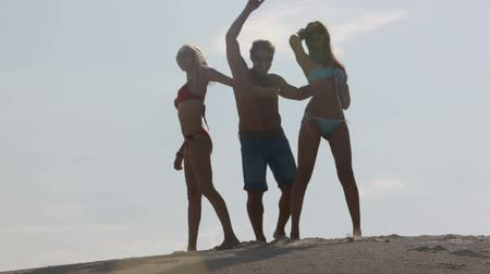 наслаждаться : Cheerful friends dancing on the beach in the light of the declining sun