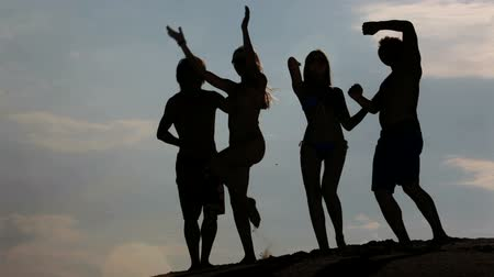 amigos : Group of active young people dancing in the dusk