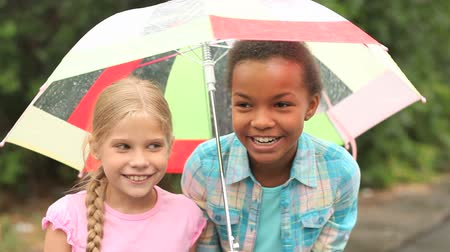 shy girl : Charming girls hanging out outside in the rain hiding under one umbrella Stock Footage
