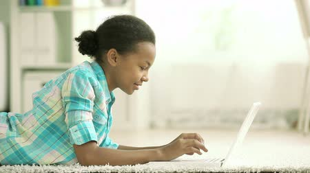 spojrzenie :  Lovely teenage girl working on her laptop then looking at the camera with a smile