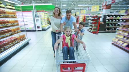 супермаркет : Family having fun in the shopping mall driving a shopping cart, one of the kids riding inside
