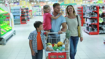 grocery : Parents and kids doing shopping together expressing their love and tenderness