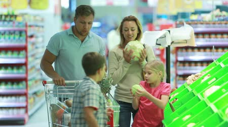 супермаркет : Family stopping by a vegetable section to take fresh cabbage