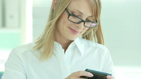 ventoso : Smiling business girl reading a funny message and texting back Stock Footage