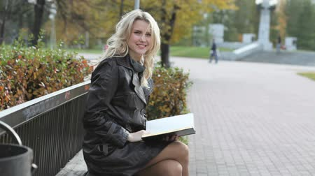 kadınlık : Young woman sitting on a park bench and reading a book