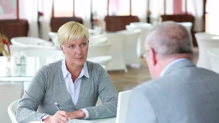 vaga : Mature businesswoman listening attentively to an applicant for a vacant position