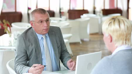 ресторан : Senior businessman interviewing a lovely lady for a job Стоковые видеозаписи