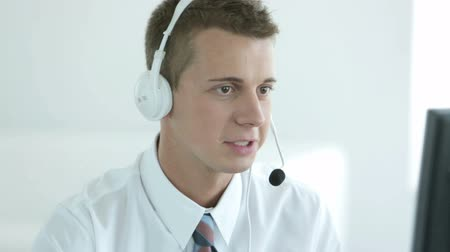 clientes : Young helpdesk operator communicating with a client via headset