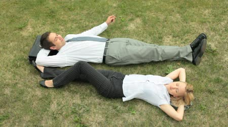 ленивый : Relaxed office workers lying on the grass enjoying warm summer day