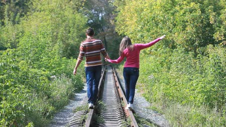 dzsungel : Guy and girl holding hands following the railways leading through the park, conceptual footage Stock mozgókép