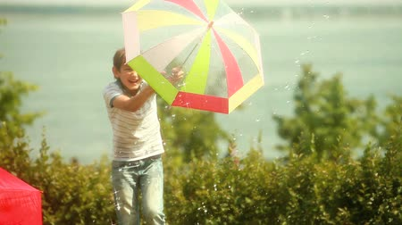 amigos : Boy holding a hose and spraying water over his friends hiding behind colorful umbrellas
