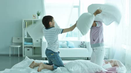 almofada : Friends spending their free time actively pillow fighting