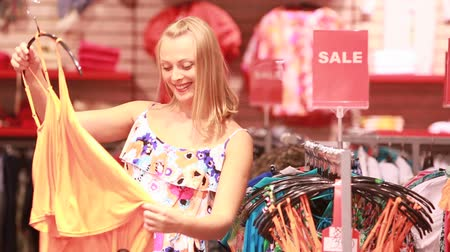 покупка товаров : Lovely blonde girl approaching the rack with clothes on sale and choosing a garment