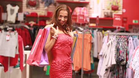 покупка товаров : Sexy lady with shopping bags showing off in front of the camera