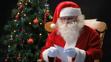 ünnepies : Santa Claus sitting in the chair and reading Christmas letters sent by children Stock mozgókép