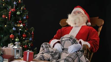 ünnepies : Santa Claus relaxing in a rocking chair having sweet dreams