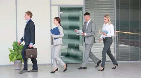 Group of business people walking confidently along the office corridor with a young leader at the head